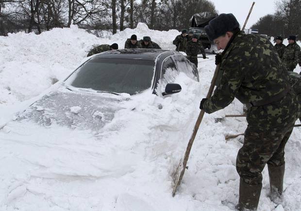 Militares desenterram carro coberto por neve nesta segunda-feira (17) na cidade ucraniana de Brody (Foto Reuters)