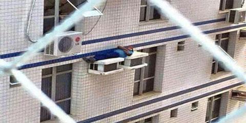 Homem é flagrado dormindo perigosamente em cima de ar-condicionado em Santa Catarina